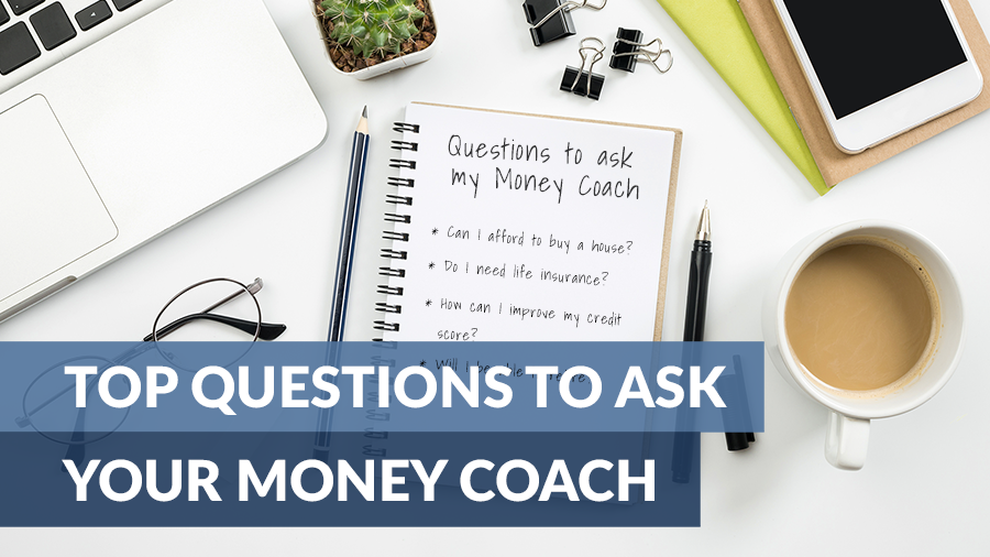 A white desk filled with a laptop, phone, pens, and a journal. The journal has questions to ask a money coach.
